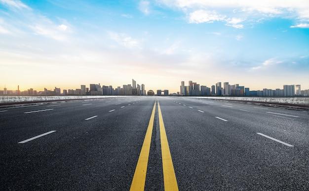 Superficie del piso de la carretera vacía con la ciudad moderna