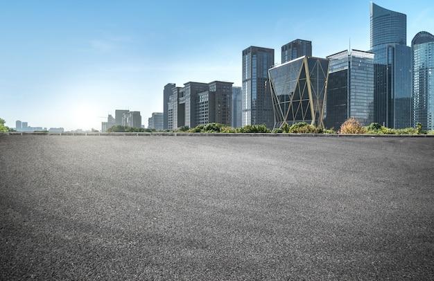 Superficie del piso de la carretera vacía con edificios emblemáticos de la ciudad moderna en china