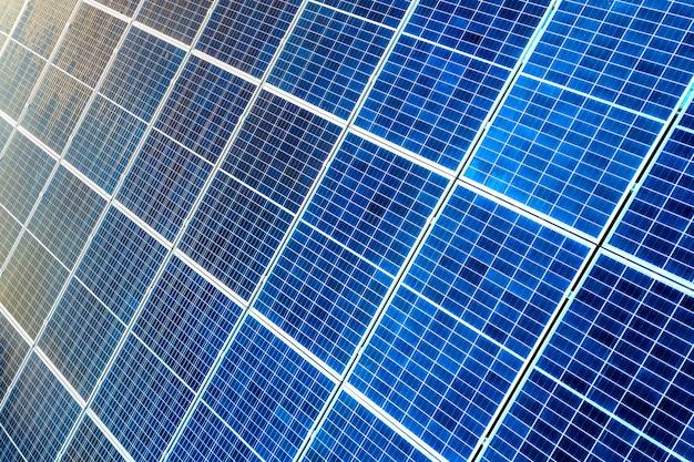 Superficie del primer de iluminado por el sol azul brillante paneles solares fotovoltaicos. sistema de producción de energías limpias renovables. concepto de producción de energía verde ecológica renovable.