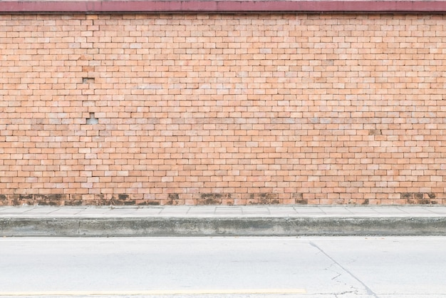 La superficie del primer del modelo del ladrillo en la pared de ladrillo marrón vieja con el piso de la calle texturizó el fondo