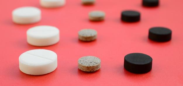 En la superficie roja hay muchas tabletas blancas, negras y marrones.