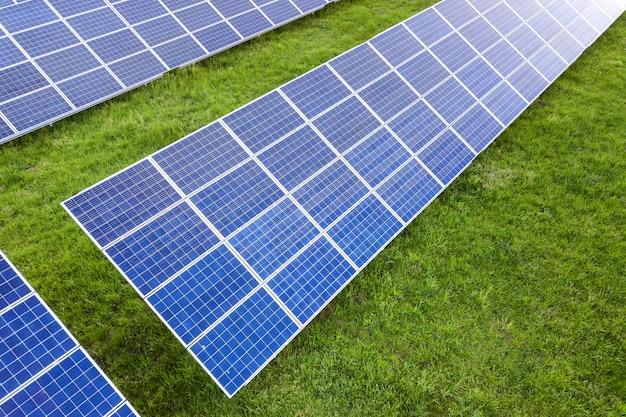 Superficie del sistema de paneles fotovoltaicos solares que produce energía limpia renovable en la hierba verde.