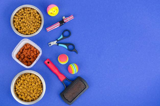 Superficie de tazones con comida, juguetes y artículos para el cuidado de mascotas, vista superior