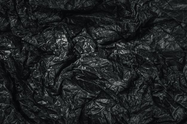 Superficie con textura de papel arrugado negro.