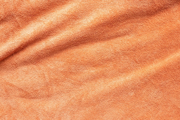 Superficie de textura de tela de toalla naranja cerca de fondo