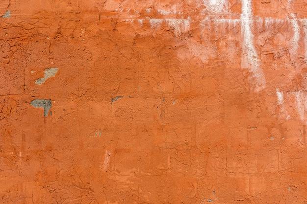 Superficie texturizada de un viejo muro de hormigón pintado de naranja