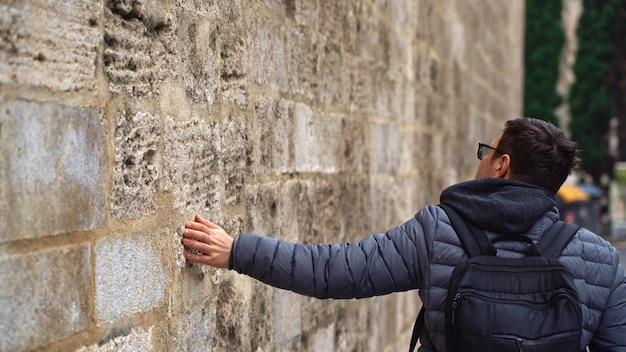 Superficie de trazo de mano de hombre, deslice sobre la pared pedregosa del antiguo edificio en el barrio gótico de barcelona, viaje