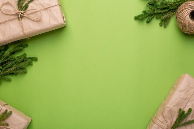Superficie verde con regalos ecológicos con plantas verdes en papel artesanal
