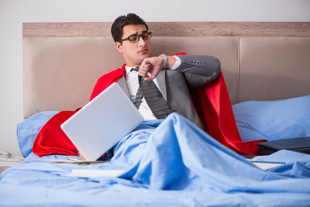 Superhéroe empresaria trabajando en la cama