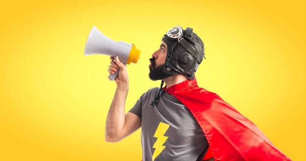 Superhéroe gritando por megáfono sobre fondo de colores