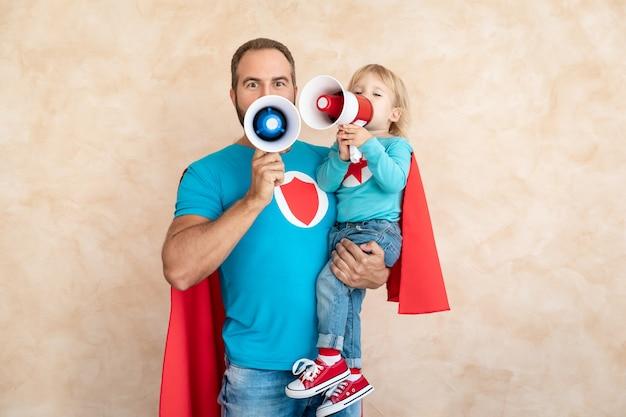 Superhéroe de hombre y niño en casa. padre e hijo de superhéroe divirtiéndose juntos.
