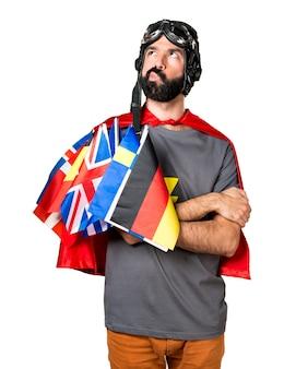 Superhéroe con un montón de banderas pensando