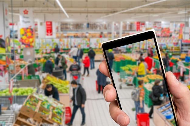 Supermercado borrosa y gente comprando en la pantalla del teléfono inteligente