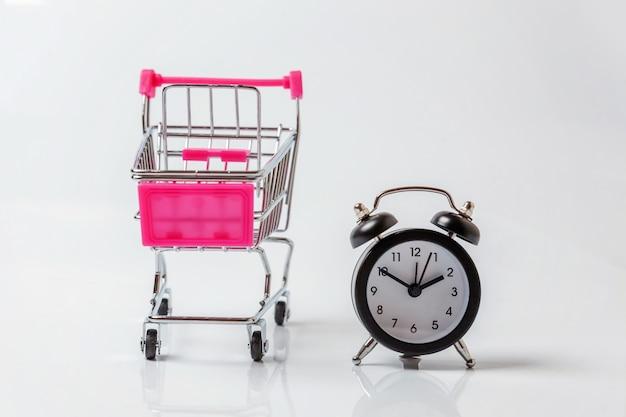 Supermercado carrito de supermercado para compras de juguetes con ruedas y despertador clásico aislado sobre fondo blanco.