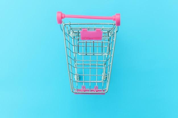 Supermercado pequeño carrito de supermercado para comprar juguetes con ruedas aisladas sobre fondo azul pastel colorido de moda copiar espacio. venta comprar centro comercial mercado tienda concepto de consumidor.