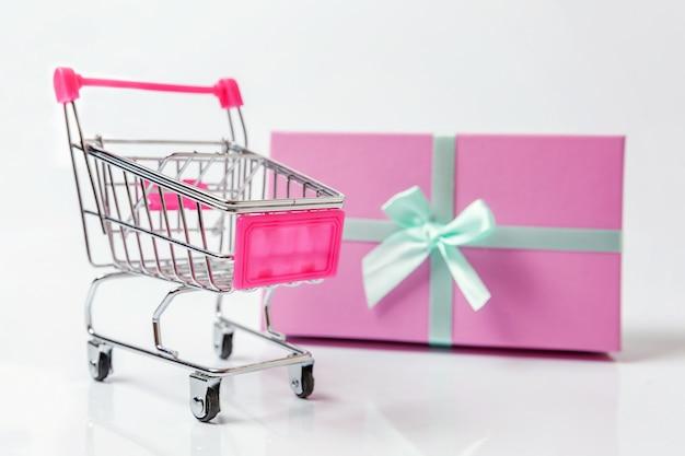 Supermercado pequeño supermercado carrito de juguete y caja de regalo sobre fondo blanco.