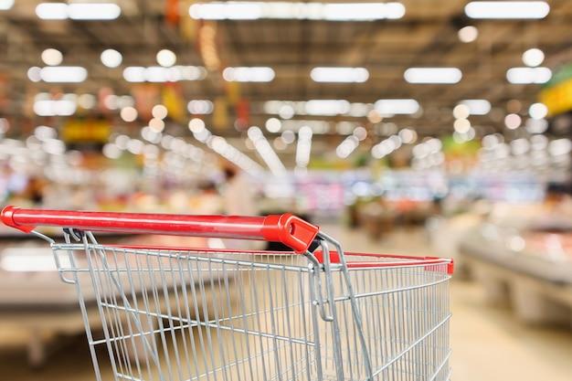 Supermercado tienda con frutas y verduras fondo desenfocado interior estantes con carrito de compras rojo vacío