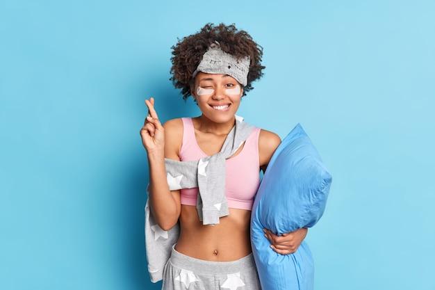 Supersticiosa mujer esperanzada en pijama cruza los dedos desea lo mejor, muerde los labios mira alegremente a la cámara sostiene la almohada usa parches de hidrogel debajo de los ojos posa sobre una pared azul