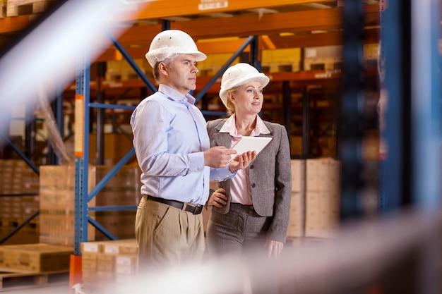 Supervisión profesional. gente agradable e inteligente parados juntos mientras observan el proceso de trabajo en el almacén