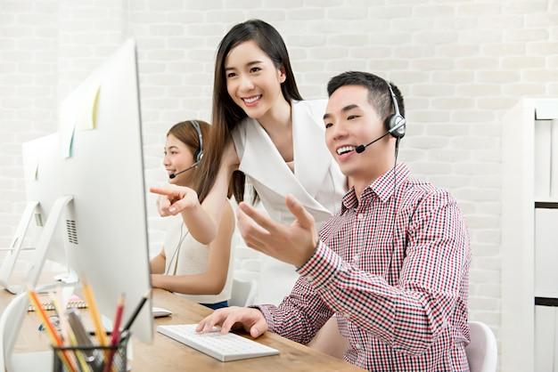 Supervisor asiático femenino discutiendo el trabajo con su equipo en call center