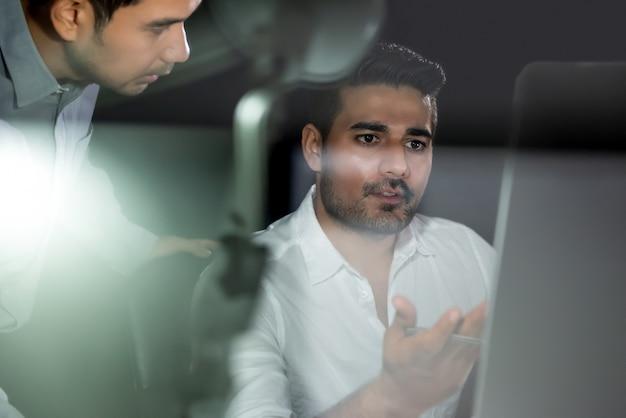 Supervisor asiático del hombre de negocios que trabaja con el equipo que discute proyecto en la noche