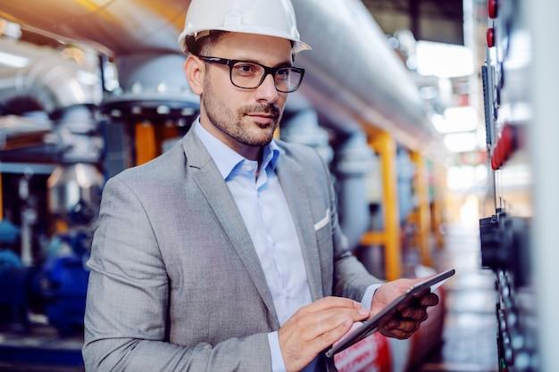 Supervisor caucásico guapo enfocado en traje y con casco en la cabeza usando tableta y mirando el tablero mientras está parado en la planta de energía.