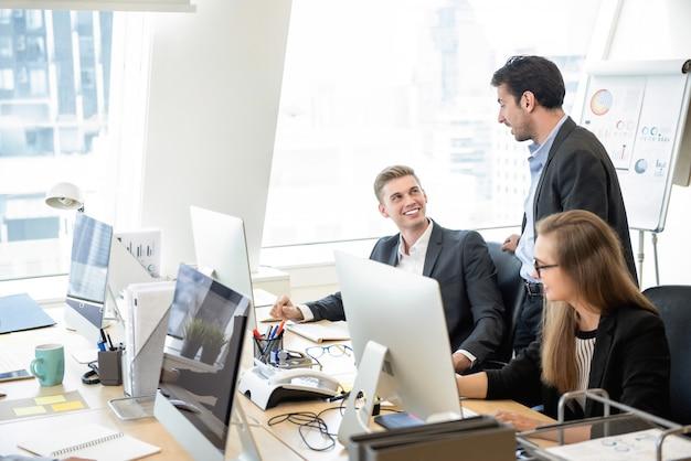 Supervisor de hombre de negocios hablando con el equipo en la oficina