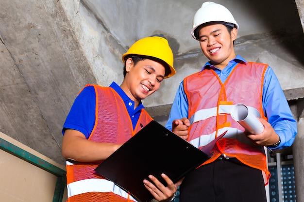 Supervisor o controlador chino y trabajador o arquitecto miran el sitio de construcción en un portapapeles