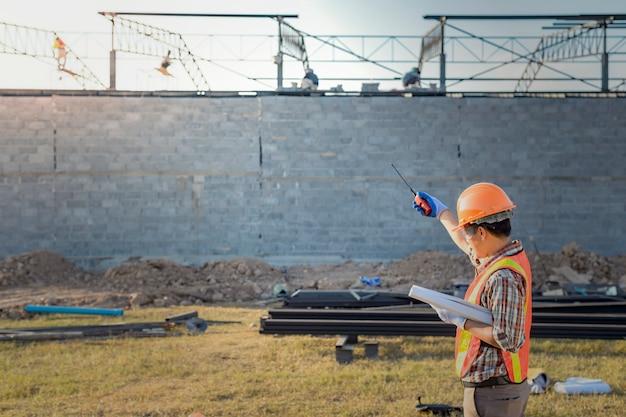 El supervisor está ordenando a los trabajadores que completen la construcción de acuerdo con el plan.