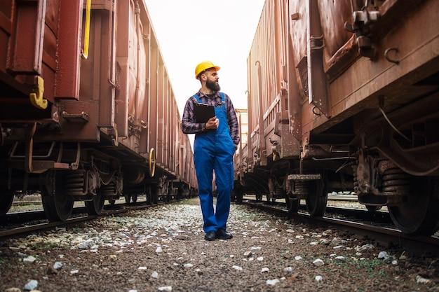 Supervisor de transporte ferroviario comprobando trenes y carga