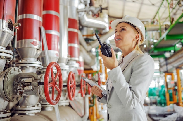 Supervisora trabajadora experimentada de mediana edad con casco en traje sosteniendo tableta en manos y hablando por walkie talkie con el empleado mientras está de pie en la planta de calefacción.