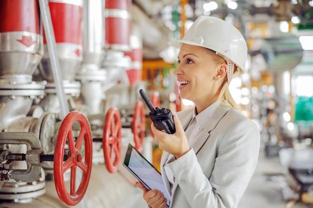 Supervisora trabajadora experimentada de mediana edad con casco en traje sosteniendo la tableta en las manos y hablando por un walkie talkie con el empleado mientras está de pie en la planta de calefacción