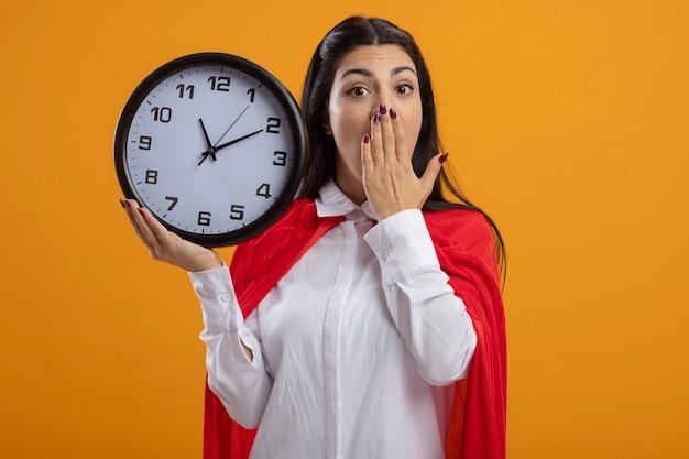 Superwoman joven sorprendida que sostiene el reloj mirando al frente manteniendo la mano en la boca aislada en la pared naranja