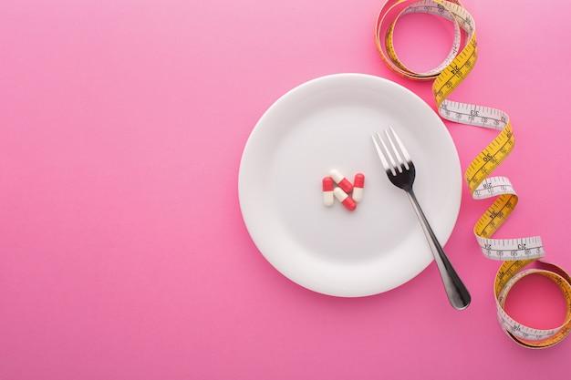 Suplemento dietético en placa con cinta métrica en rosa, vista superior