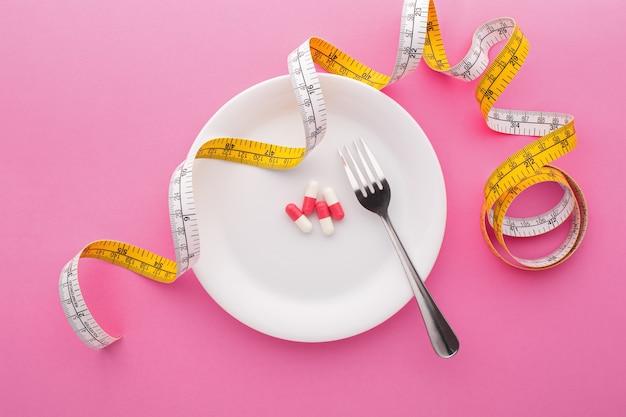 Suplemento dietético en placa con cinta métrica, vista superior