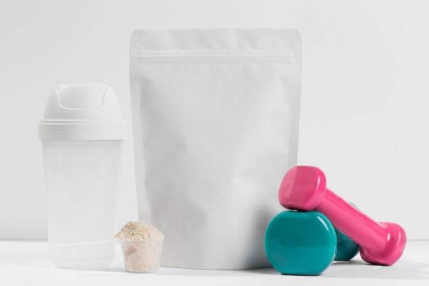 Suplemento para jarra de gimnasio con pesas en la mesa