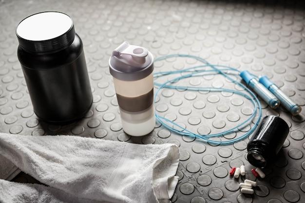 Suplementos y cuerda en el suelo en el gimnasio crossfit.