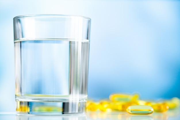 Suplementos de vitaminas y aceite de pescado en cápsulas amarillas con vaso de agua.