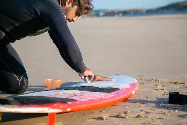 Surfer guapo centrado en traje de neopreno pulido tabla de surf con cera sobre arena.