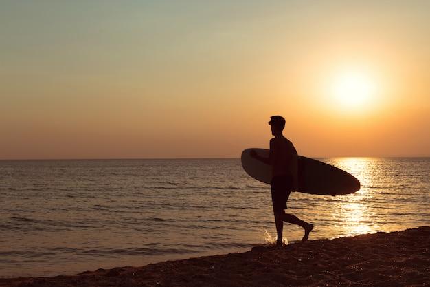Un surfista al atardecer.