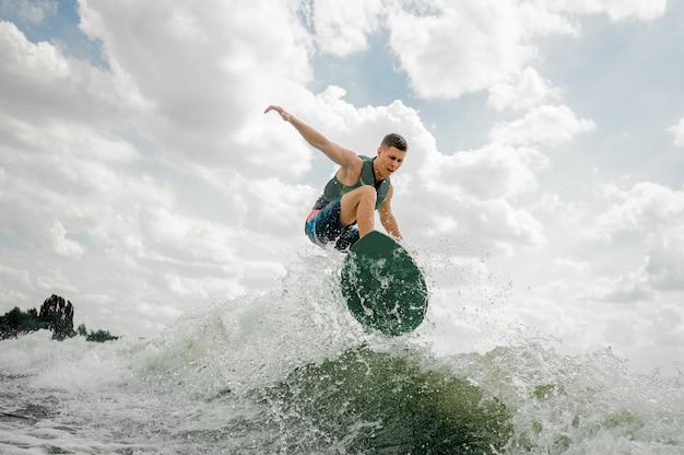 Surfista caucásico montando wakeboard en onda alta
