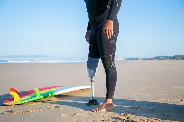 Surfista masculino vistiendo traje de neopreno y una extremidad artificial, de pie junto a la tabla de surf sobre arena.