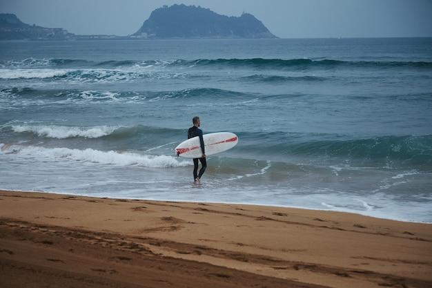 Surfista de mediana edad en traje de neopreno caminando hacia el agua en la playa de arena entre colinas