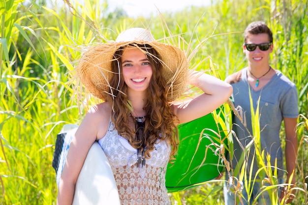 Surfista de niña con sombrero de playa caminando con tabla de surf