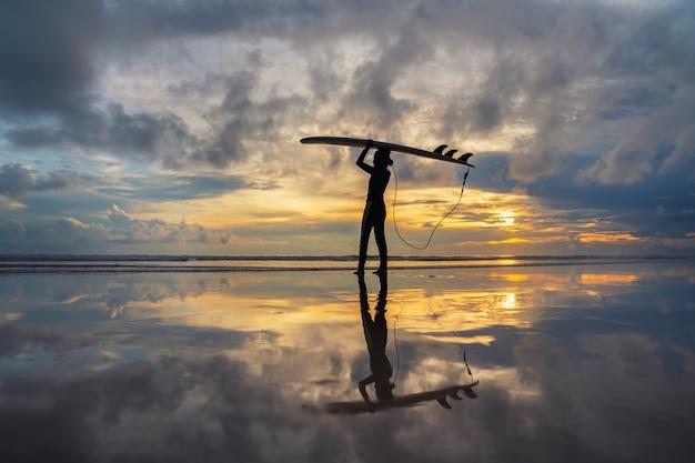 Surfista niña surfeando en la playa del océano puesta de sol