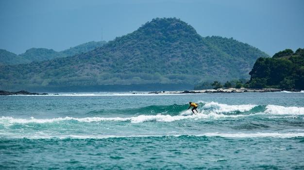 Surfista en una ola azul.