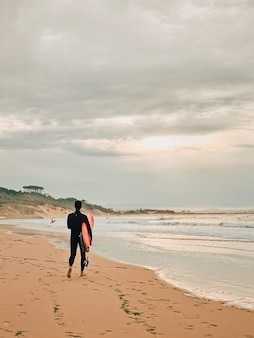 Surfista en la playa de arena