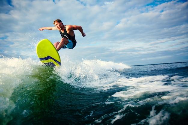 Surfista valiente montando una ola