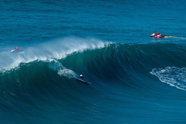 Los surfistas cabalgando sobre las olas del océano atlántico hacia la orilla en nazaré, portugal