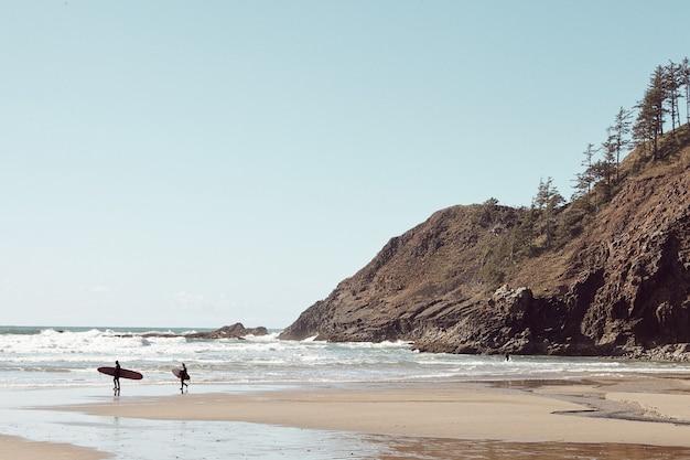 Surfistas en la distancia en la playa rocosa